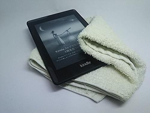 Kindle paperwhiteの画面をタオルで拭いている様子
